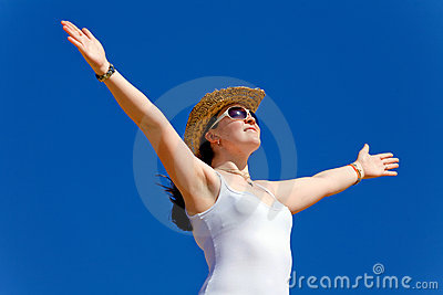 Girl with open arms over a blue sky - freedom