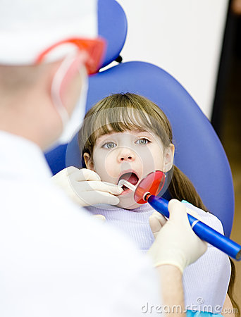 Girl with open mouth receiving dental filling dryi
