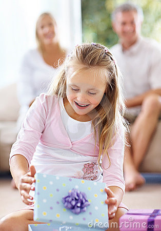Girl opening gift box with her parents at back