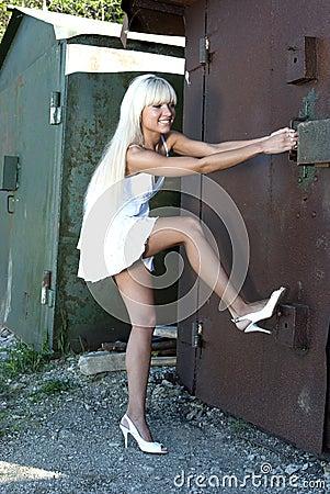 Girl opens old garage Stock Photo