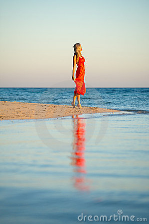 Girl in orange dress by seas edge