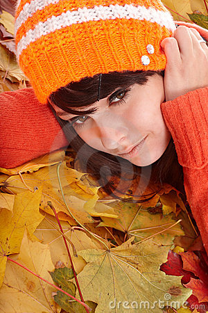 Girl in orange hat on leaves with sad face.