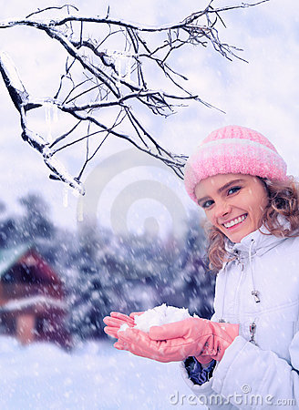 Girl outdoor in winter holds snow in hands