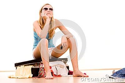 Girl on overstuffed suitcase