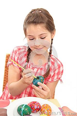 Girl painting an egg