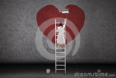 Girl painting love on the wall