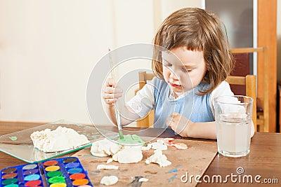 Girl paints dough figurines Stock Photo