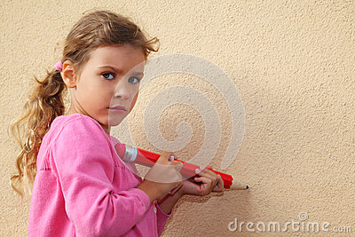 Girl paints by pencil on wall