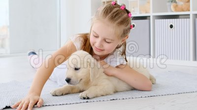 Girl palming cute puppy. School girl palming cute puppy lying on carpet stock footage