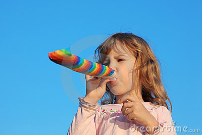 Girl with party blower on blue sky