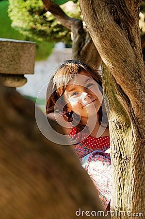 Girl Peeking Around Tree