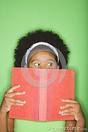 Girl peeking over book.