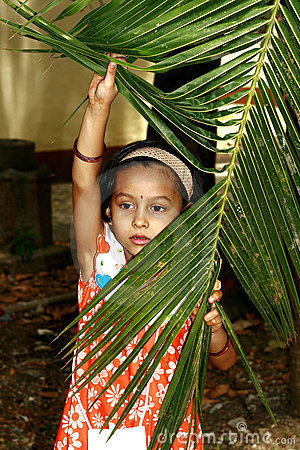 Girl peeking through palm
