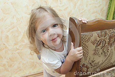 Girl peeks out from behind the chair