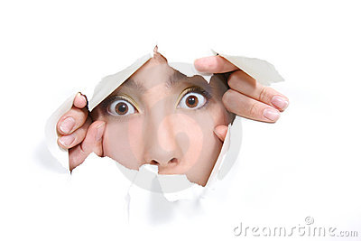 Girl peeping through hole in white paper