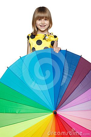 Girl peeping out from behind the colorful umbrella