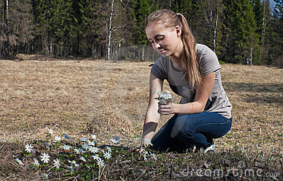 A girl picking snowdrops.