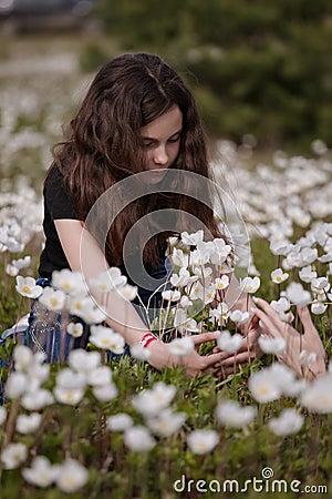 Girl picking white poppies
