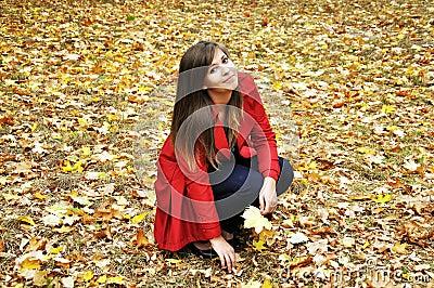 Girl picks up the maple leaves