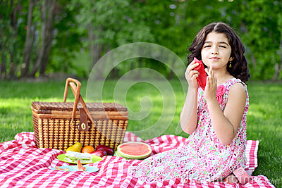 Girl at picnic using red napkin
