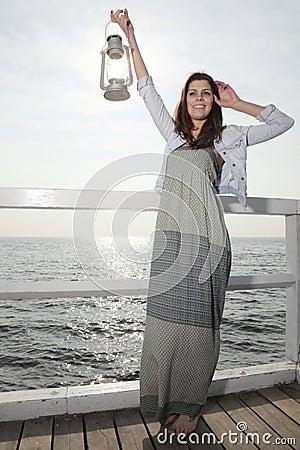 Girl on pier with kerosene lamp