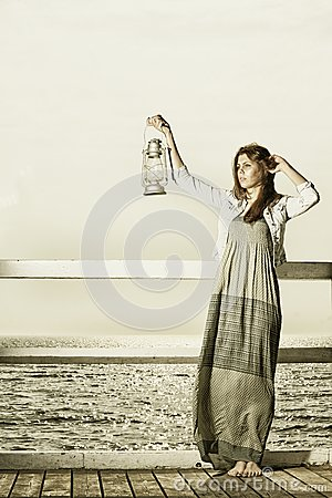 Girl on pier with kerosene lamp