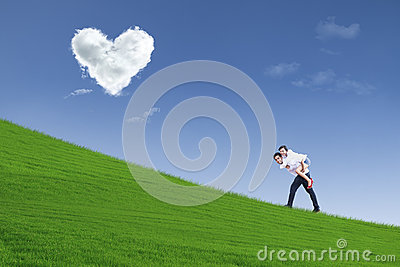 Girl on piggyback ride under heart clouds