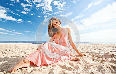 Girl in pink dress on seacoast