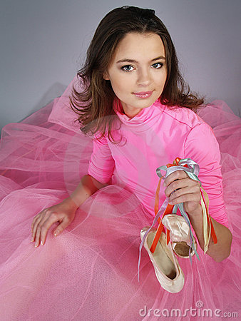 girl in a pink dress shows footwear