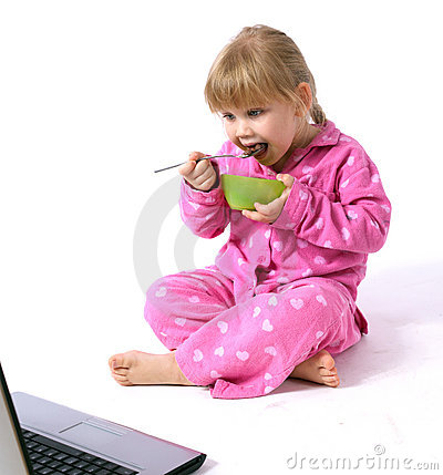 Girl in pink pajamas eating cereal