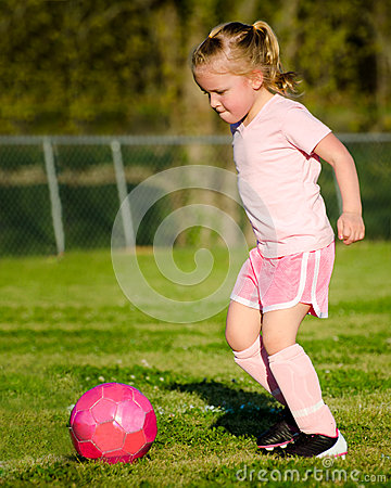 Girl in pink playing soccer on field