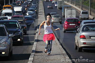 Girl in pink skirt runs on highway middle