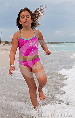 Girl on a pink swimsuit running on a beach