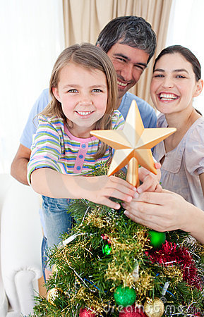 Girl placing a Christmas star on the top of a tree