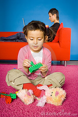 Girl is plaing with toy blocks (mother behind her)