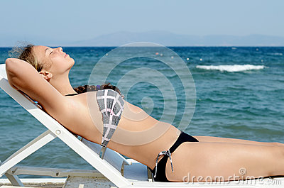 Girl on a plank bed at the sea