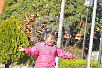 A girl play with dry leaves