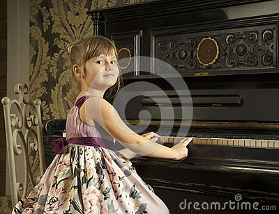 Girl play the piano and look back