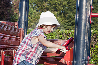 Girl at playground in wooden car