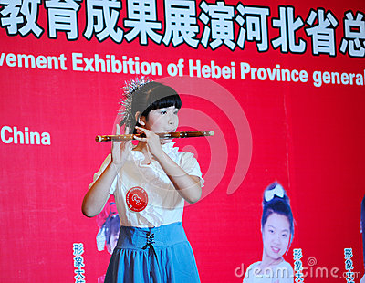 Girl in playing the bamboo flute Editorial Image