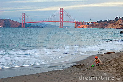Girl playing on the beach at sunset and Golden Gate Bridge