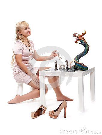 girl playing chess with a decorative dragon