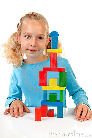Girl is playing with colorful wooden blocks