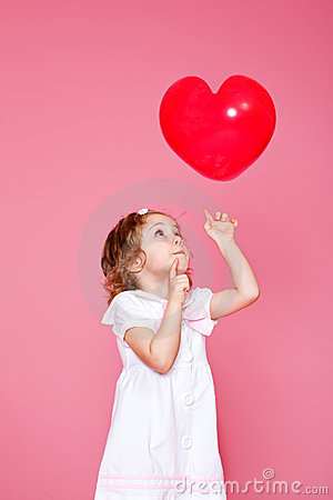 Girl playing with heart shaped balloon