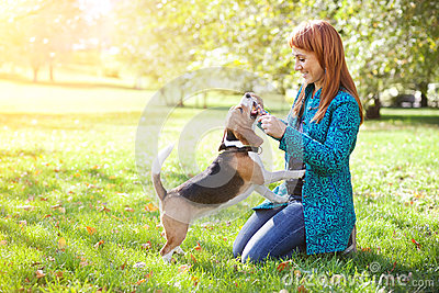 Girl playing with her dog in autumn park