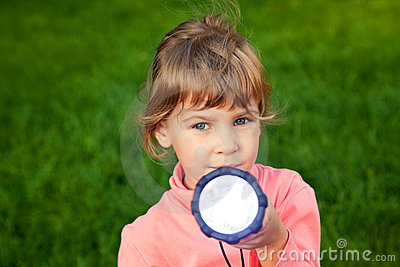 Girl playing with lantern on grass