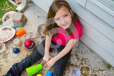 Girl playing with mud in a messy soil smiling portrait