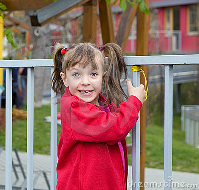 Girl playing near fence