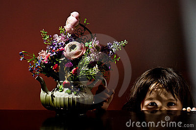 Girl playing peek-a-boo with flowers