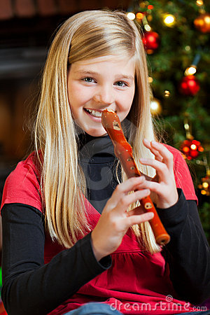 Girl playing recorder on christmas eve